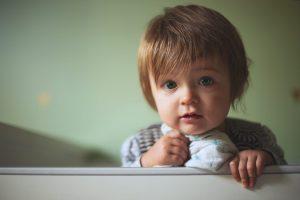 Toddler standing awake in bed holding blankie