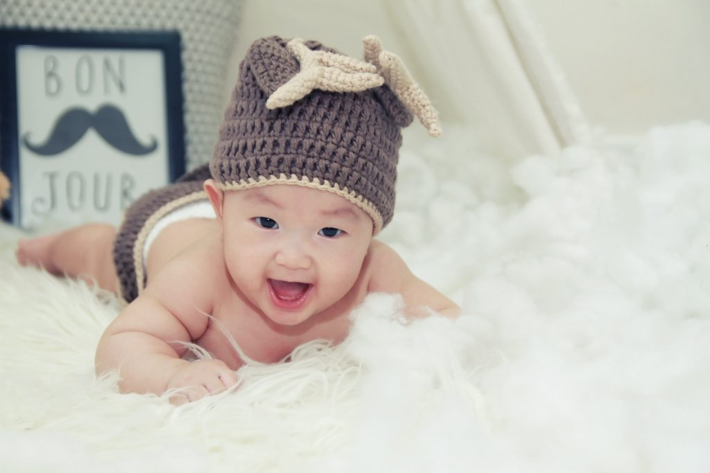 Adorable asian baby with beanie lying on furry carpet with bon jour sign