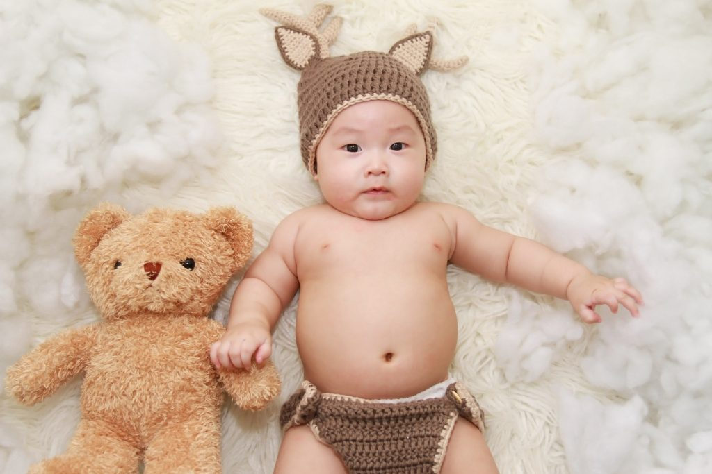 Adorable asian boy with knitted fox ear beanie holding teddy bear