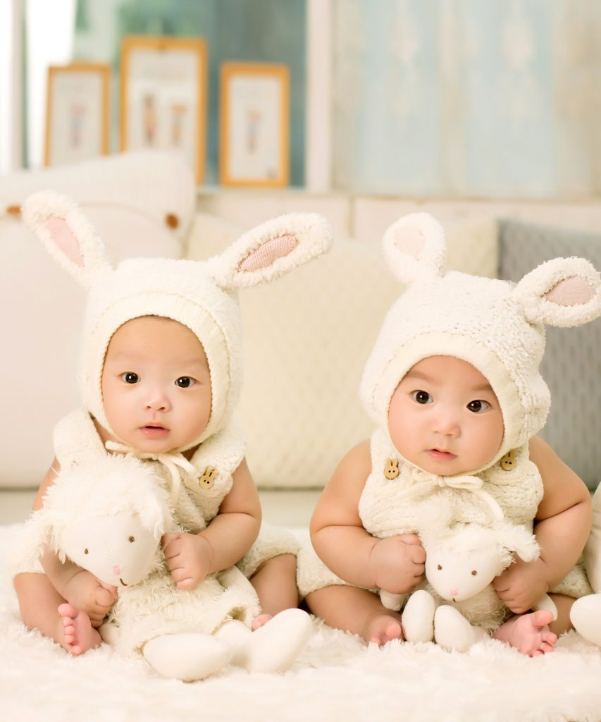 Adorable asian babies in bunny costumes holding lambs on a bed