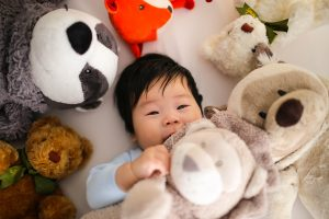Asian baby boy covered and surrounded by teddy bears lying in bed
