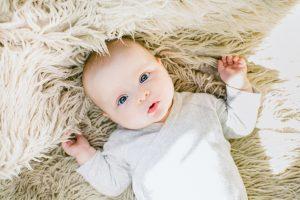 Beautiful baby lying on fur blanket with eyes open