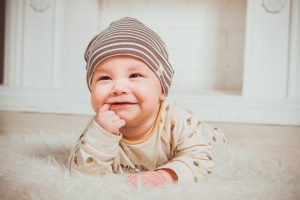 Adorable, happy baby boy having tummy time while chewing on his finger