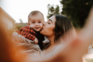 Mom kissing adorable baby boy in plaid jacket