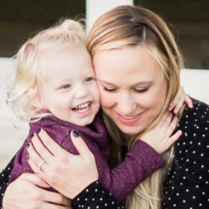 blonde mom and blonde 1 year old daughter hugging and smiling