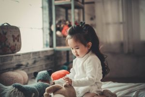 Beautiful asian toddler girl playing with stuffed animals on bed