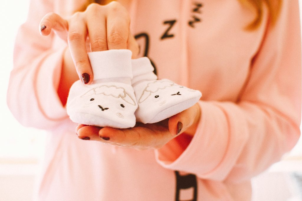 Mom holding newborn baby lamb shoes wearing sleepy pajamas