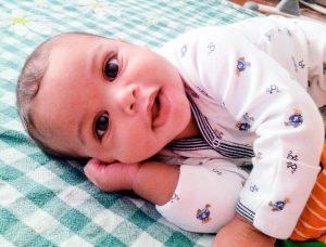Adorable baby boy lying on plaid blanket