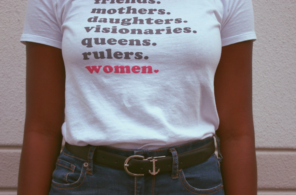 Woman wearing shirt reading friends, mothers, daughters, visionaries, queens, rulers, women