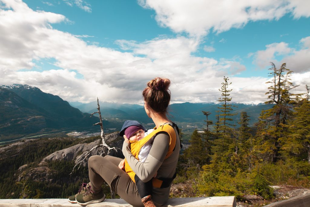 Hiking mom wearing baby over beautiful vista