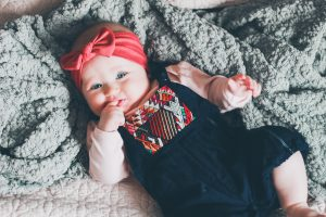 baby girl head band finger in mouth