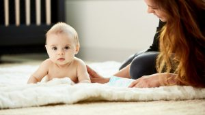 adorable baby on soft rug lying next to mom with crib behind them