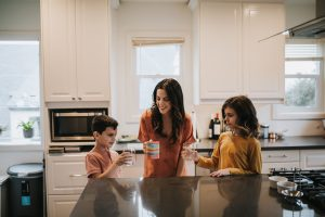 Natalie Willes and her two children in a kitchen doing cheers with mugs